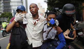 Paramedics assist a man injured during clashes with security forces during protests asking for the resignation of President Nicolas Maduro in Caracas, Venezuela, Thursday, April 20, 2017. Tens of thousands of protesters flooded the streets again Thursday, one day after three people were killed and hundreds arrested in the biggest anti-government demonstrations in years. (AP Photo/Ariana Cubillos)