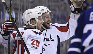 CORRECTS CREDIT TO GOAL SCORED TO TOM WILSON NOT LARS ELLER Washington Capitals center Lars Eller (20) celebrates a goal scored by teammate Tom Wilson, right, during first period NHL hockey round one playoff action against the Washington Capitals, in Toronto on Wednesday, April 19, 2017. (Frank Gunn/The Canadian Press via AP)