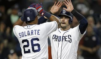 San Diego Padres' Yangervis Solarte, left, and Austin Hedges congratulate each other for scoring on a two-run double by Erick Aybar against the Arizona Diamondbacks during the fifth inning of a baseball game in San Diego, Thursday, April 20, 2017. (AP Photo/Alex Gallardo)