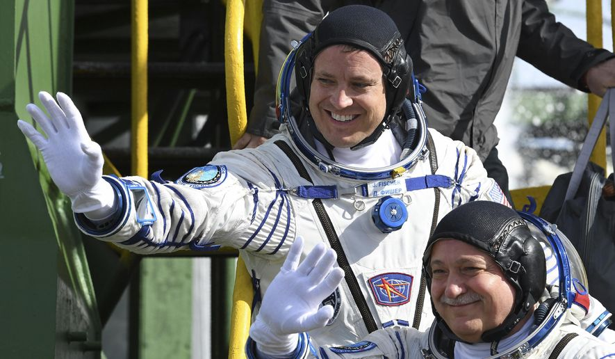 U.S. astronaut Jack Fischer, above, and Russian cosmonaut Fyodor Yurchikhin, crew members of the mission to the International Space Station, ISS, wave near the rocket prior the launch of Soyuz-FG rocket at the Russian leased Baikonur cosmodrome, Kazakhstan, Thursday, April 20, 2017. (AP Photo/Kirill Kudryavtsev, Pool)
