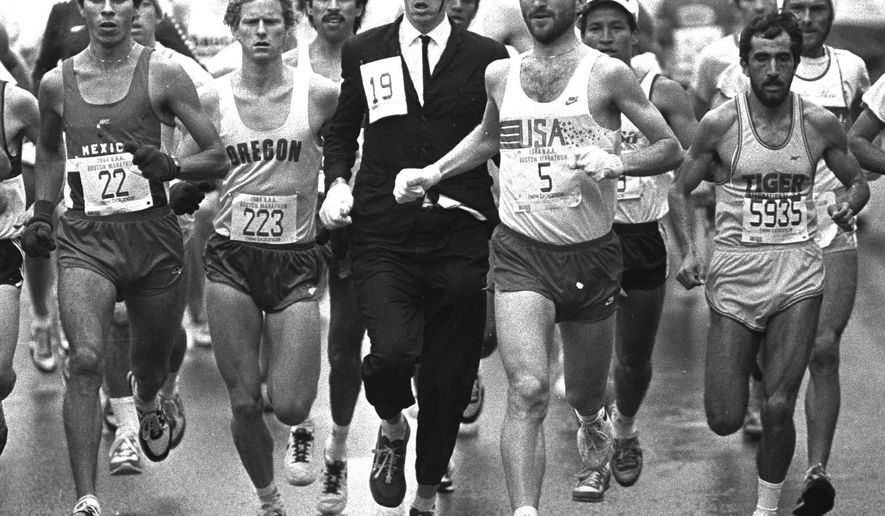 FILE - In this Monday, April 17, 1984, file photo, an unidentified man wearing a business suit and black hat, runs with the Boston Marathon pack along the course from Hopkinton to Boston, flanked by D.J. Harding (223) of Oregon, and Tom Fleming (5) of New Jersey. Fleming, a two-time winner of the New York City Marathon, died Wednesday, April 19, 2017, while coaching his New Jersey middle school team at a meet, in Verona, N.J. (AP Photo/File)