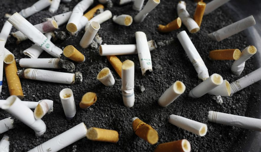 FILE - In this April 7, 2017, file photo, cigarette butts are discarded in an ashtray outside a New York office building. New York City Mayor Bill de Blasio announced a plan on April 19, 2017, to raise the price of a pack of cigarettes from $10.50 to $13 in the city. (AP Photo/Mark Lennihan, File)