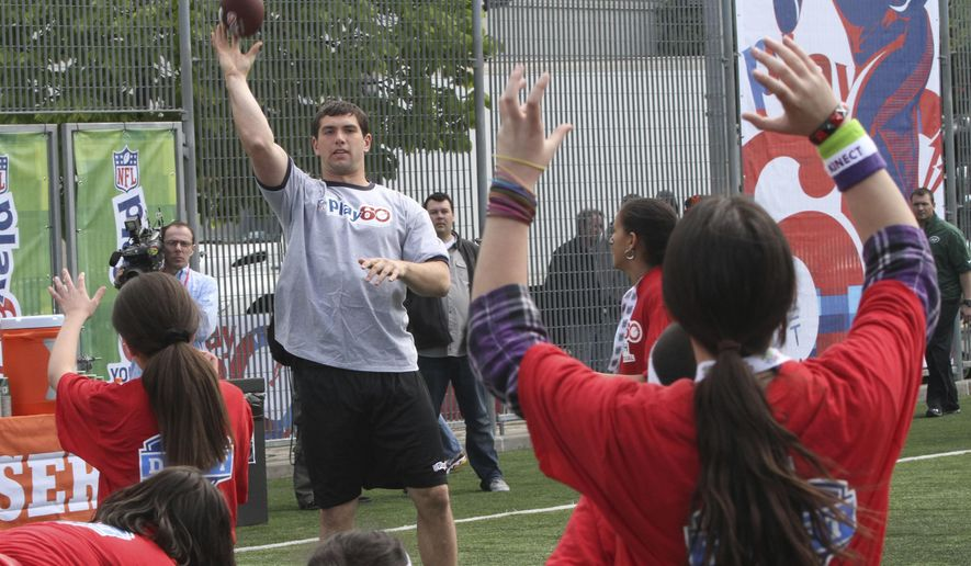 FILE - In this April 25, 2012, file photo, Andrew Luck, center left, throws the ball during the NFL Play 60 Youth Football Festival in New York. When the NFL launched Play 60 a decade ago as a way to get American youth active, the league had no idea what kind of reach the program would have. Ten years later, millions of youngsters and 73,000 schools have become involved, and affiliations with such organizations as the American Heart Association and the National Dairy Council have helpoed make Play 60 one of the nation's most effective anti-obesity and children's activity initiatives in the land.(AP Photo/Mary Altaffer, File)