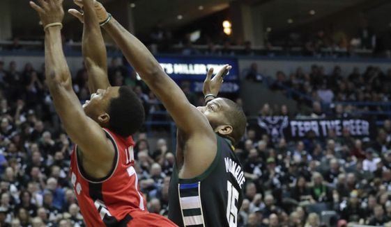 Milwaukee Bucks' Greg Monroe blocks the shot of Toronto Raptors' Kyle Lowry during the first half of game 3 of their NBA first-round playoff series basketball game Thursday, April 20, 2017, in Milwaukee. (AP Photo/Morry Gash)