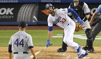 Los Angeles Dodgers' Scott Van Slyke, center, watches his solo home run off Colorado Rockies starting pitcher Tyler Anderson, left, as catcher Dustin Garneau stands at rear during the second inning of a baseball game, Wednesday, April 19, 2017, in Los Angeles. (AP Photo/Mark J. Terrill)