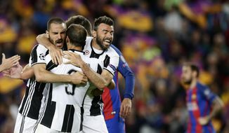 Juventus' Leonardo Bonucci, left, celebrates with teammates Giorgio Chiellini, center, and Andrea Barzagli during the Champions League quarterfinal second leg soccer match between Barcelona and Juventus at Camp Nou stadium in Barcelona, Spain, Wednesday, April 19, 2017. (AP Photo/Manu Fernandez)