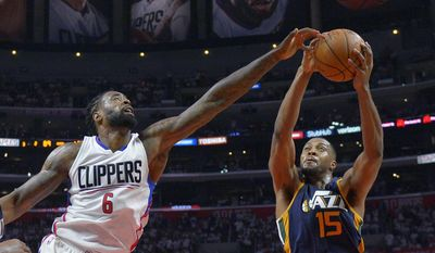 FILE - In this Saturday, April 15, 2017, file photo, Utah Jazz forward Derrick Favors, right, grabs a rebound away from Los Angeles Clippers center DeAndre Jordan during the second half in Game 1 of an NBA basketball first-round playoff series, in Los Angeles. Favors became the forgotten man in Utah as Gordon Hayward and Rudy Gobert posted career years. The former No. 3 overall pick had his worst season in years as he was sapped of his athleticism by a knee injury that limited him to just 50 regular season games. Gobert went down with a knee injury 11 seconds into Game 1 against the Clippers and the Jazz now need Favors more than ever against the duo of Jordan and Blake Griffin. (AP Photo/Mark J. Terrill, File)
