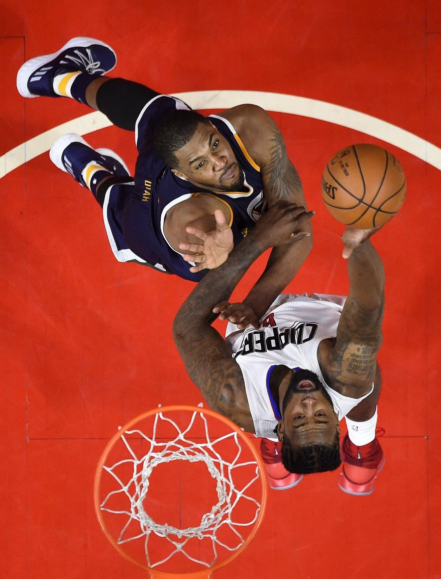 FILE - In this Saturday, April 15, 2017, file photo, Los Angeles Clippers center DeAndre Jordan, foreground, shoots as Utah Jazz forward Derrick Favors defends during the second half in Game 1 of an NBA basketball first-round playoff series, in Los Angeles. Favors became the forgotten man in Utah as Gordon Hayward and Rudy Gobert posted career years. The former No. 3 overall pick had his worst season in years as he was sapped of his athleticism by a knee injury that limited him to just 50 regular season games. Gobert went down with a knee injury 11 seconds into Game 1 against the Clippers and the Jazz now need Favors more than ever against the duo of DeAndre Jordan and Blake Griffin. (AP Photo/Mark J. Terrill, File)