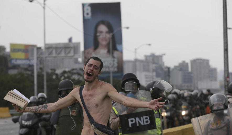 An anti-government protester holds a bible under the watch of riot police during a march in Caracas, Venezuela, Thursday, April 20, 2017. Tens of thousands of protesters flooded the streets again, one day after three people were killed and hundreds arrested in the biggest anti-government demonstrations in years. (AP Photo/Fernando Llano)