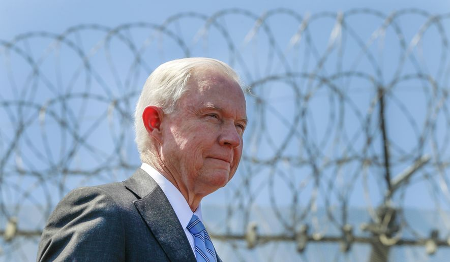 With razor wire across the top of the secondary border fence behind him, United States Attorney General Jeff Sessions stands during a news conference at the U.S.-Mexican border next to the Brown Field Border Patrol Station in San Diego on Friday, April 21, 2017. (Hayne Palmour IV/The San Diego Union-Tribune via AP) ** FILE **
