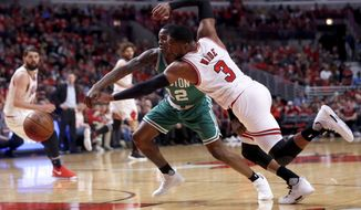 Chicago Bulls' Dwyane Wade (3) and Boston Celtics' Terry Rozier battle for a loose ball during the first quarter of Game 3 of a first-round NBA playoff basketball series in Chicago, Friday, April 21, 2017. (AP Photo/Charles Rex Arbogast)