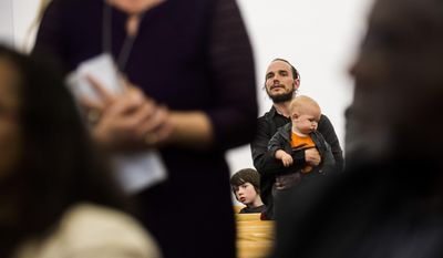 In this Thursday, April 20, 2017, photo, Flint resident Adam Murphy and two of his children listen closely after his wife, Christina, voiced her opinions in ongoing issues with the Flint water crisis during a town hall meeting at House of Prayer Missionary Baptist Church, in Flint, Mich. (Jake May/The Flint Journal-MLive.com via AP)