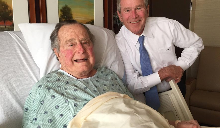 This Thursday, April 20, 2017, photo provided by the Office of George H.W. Bush shows former President George H.W. Bush, left, posing with his son former President George W. Bush at Houston Methodist Hospital in Houston where he is recovering from a mild case of pneumonia. He was admitted to the hospital Friday, April 14 for treatment of a persistent cough and doctors determined he had pneumonia. (Evan Sisley/Office of George H.W. Bush via AP)