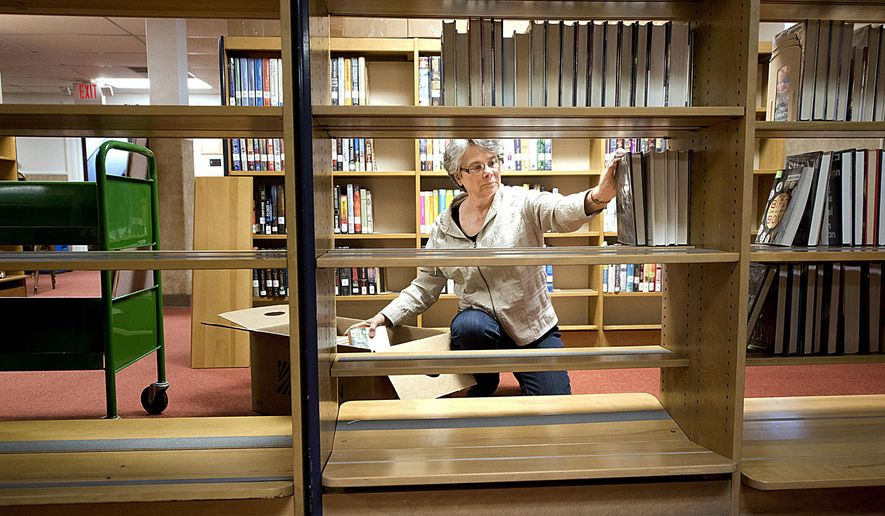 In this Thursday, April 20, 2017 photo, Rosanne Hoss puts books onto a shelf at the Le Mars Public Library's temporary location in the Eagle's Club building, in Le Mars, Iowa. Volunteers are moving the library's collection across the street from the library to the Eagles before the start of a $350,000 renovation project at the library building. The renovations are expected to be finished in September. (Tim Hynds/Sioux City Journal via AP)