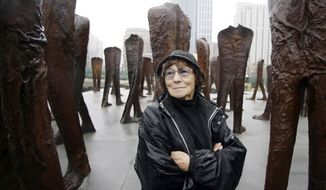 FILE - In this file photo taken Oct. 26, 2006, Polish sculptor Magdalena Abakanowicz stands before several of the 106 cast iron human figures, each nine feet tall, she created, as they were being installed in Chicago's Grant Park. Adam Myjak, the rector of Fine Arts Academy in Warsaw, Poland said on Friday, April 21, 2017, that Abakanowicz has died. She was 86-years-old. (AP Photo/M. Spencer Green, file)