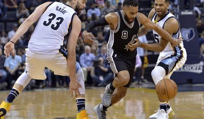 San Antonio Spurs guard Patty Mills (8) loses control of the ball while driving between Memphis Grizzlies center Marc Gasol (33) and guard Andrew Harrison (5) during the second half of Game 3 in an NBA basketball first-round playoff series Thursday, April 20, 2017, in Memphis, Tenn. (AP Photo/Brandon Dill)