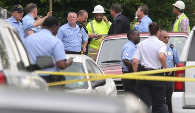 St. Louis police and Laclede Gas Co. workers congregate after a fatal shooting Thursday, April 20, 2017, in St. Louis. Manyika McCoy had just been talking to two Laclede Gas Co. workers just before they were killed by a man who walked up and started shooting. (J.B. Forbes/St. Louis Post-Dispatch via AP)