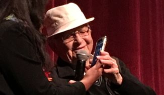 "Norman Lear takes a call on his phone from filmmaker Heidi Ewing, who co-directed the documentary ""Norman Lear: Just Another Version of You,"" live during a Q&A at Ebertfest Sunday, April 22, 2017, in Champaign-Urbana, Illinois.  (Eric Althoff/The Washington Times)"