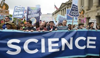People carry a banner and signs as they pass the U.S. Environmental Protection Agency during the March For Science in Washington, Saturday, April 22, 2017. Scientists, students and research advocates rallied from the Brandenburg Gate to the Washington Monument on Earth Day, conveying a global message of scientific freedom without political interference and spending necessary to make future breakthroughs possible.  (AP Photo/Sait Serkan Gurbuz)