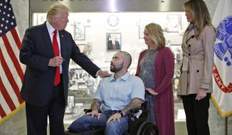 President Donald Trump prepares to award a Purple Heart to U.S. Army Sgt. 1st Class Alvaro Barrientos, with first lady Melania Trump, right, and Tammy Barrientos, second from right, at Walter Reed National Military Medical Center, Saturday, April 22, 2017, in Bethesda, Md. (AP Photo/Alex Brandon)