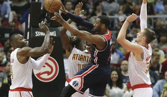 Washington Wizards' John Wall passes off under the basket on a triple-team by Atlanta Hawks defenders Paul Millsap, Tim Hardaway Jr. and Mike Muscala, from left, during Game 3 of an NBA basketball first-round playoff series Saturday, April 22, 2017, in Atlanta. (Curtis Compton/Atlanta Journal-Constitution via AP)