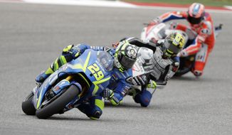 Andrea Iannone (29), of Italy, Karel Abraham (17) and Danilo Petrucci (9), of Italy, steer through a turn during open practice for the Grand Prix of the Americas MotoGP motorcycle race, Saturday, April 22, 2017, in Austin, Texas. (AP Photo/Eric Gay)