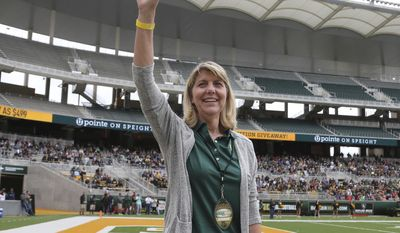 Baylor's new president Linda A. Livingstone waves to the fans as she is introduced during the first half of the NCAA college football team's Green and Gold spring game, Saturday, April 22, 2017, in Waco, Texas. (Jerry Larson/Waco Tribune Herald via AP)