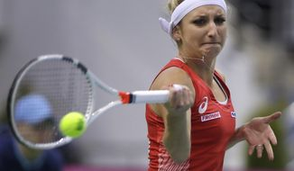 Timea Bacsinszky, of Switzerland, returns a ball to Aryna Sabalenka, of Belarus, during the Fed Cup World Group semi final tennis match between Belarus and Switzerland, in Minsk, Belarus, Saturday, April 22, 2017. (AP Photo/Sergei Grits)