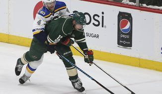 Minnesota Wild's Eric Staal (12) tries to control the puck against St. Louis Blues' Carl Gunnarsson (4) during the second period of Game 5 of an NHL hockey Stanley Cup first-round playoff series Saturday, April 22, 2017, in St. Paul, Minn. (AP Photo/Stacy Bengs)