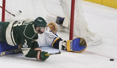 St. Louis Blues goalie Jake Allen reaches out to block the puck next to Minnesota Wild's Charlie Coyle (3) during the second period of Game 5 of an NHL hockey Stanley Cup first-round playoff series Saturday, April 22, 2017, in St. Paul, Minn. (AP Photo/Stacy Bengs)