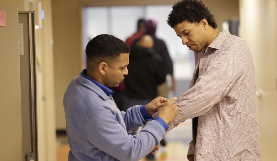 In this Thursday, April 20, 2017 photo, Neftali Thomas Diaz, right, tries on donated work clothes with the help of his case manager David Rodriguez, at The Fortune Society in New York. At the Fortune Society, one of the social service nonprofits expected to partner with the city on the plan and a sponsor of Diaz, the mission is proving the critics wrong by training former state prison and jail inmates on how to land and keep jobs. (AP Photo/Seth Wenig)