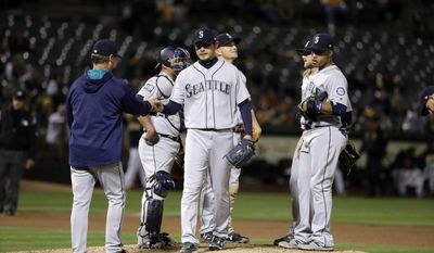 Seattle Mariners starting pitcher Hisashi Iwakuma, center, is pulled from the baseball game by manager Scott Servais during the sixth inning against the Oakland Athletics on Friday, April 21, 2017, in Oakland, Calif. (AP Photo/Marcio Jose Sanchez)