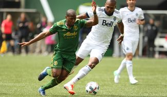 Portland Timbers' Darlington Nagbe, left, fights to get free before scoring a first-half goal during an MLS soccer game against the Vancouver Whitecaps, Saturday, April 22, 2017, in Portland, Ore. (Pete Christopher/The Oregonian via AP)