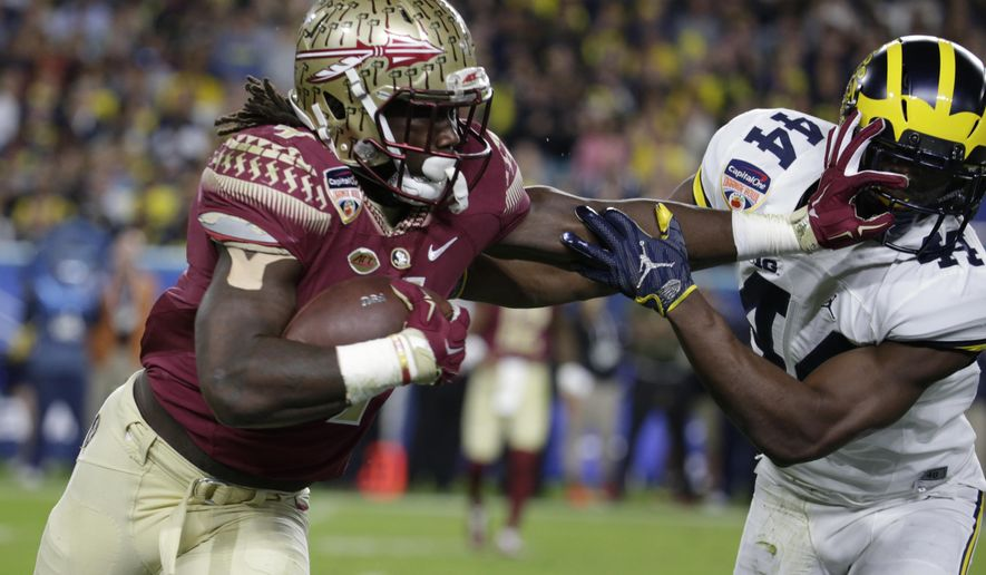 FILE - This Dec. 30, 2016, file photo shows Michigan safety Delano Hill, right, attempting to stop Florida State running back Dalvin Cook, left, during the first half of the Orange Bowl NCAA college football game in Miami Gardens, Fla. Home-run hitter with big-time acceleration, but ball security has been a problem and there are questions about his ability to run between the tackles. If he slips out of the first round, Cook will be a second-round steal. (AP Photo/Lynne Sladky, File)