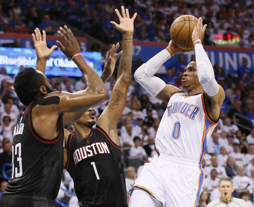 Oklahoma City Thunder guard Russell Westbrook (0) shoots as Houston Rockets guard James Harden (13) and forward Trevor Ariza (1) defend during the third quarter of a first-round NBA basketball playoff game in Oklahoma City, Friday, April 21, 2017. Oklahoma City won 115-113. (AP Photo/Sue Ogrocki)