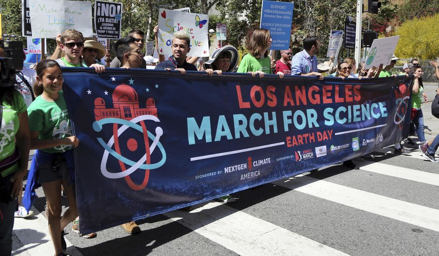 """Demonstrators take part in a rally and march in downtown Los Angeles, part of the March for Science, Saturday, April 22, 2017. They chanted """"Money for science and education, not for wars and climate alteration."""" (AP Photo/Reed Saxon)"""