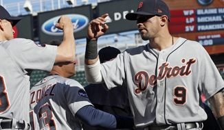 Detroit Tigers' Nicholas Castellanos, right, goes through the celebration line after the Tigers defeated the Minnesota Twins in a baseball game Saturday, April 22, 2017, in Minneapolis. (AP Photo/Jim Mone)