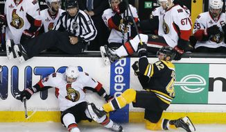 Ottawa Senators' Alex Burrows (14) and Boston Bruins' David Backes (42) fall to the ice in front of the Ottawa bench during the third period in Game 6 of a first-round NHL hockey Stanley Cup playoff series, Sunday, April 23, 2017, in Boston. (AP Photo/Michael Dwyer)