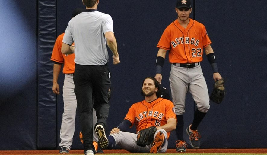 Houston Astros center fielder Jake Marisnick, center, smiles as a Houston trainer and right fielder Josh Reddick, right, check on him after he hit the wall making a catch on a deep fly ball hit by Tampa Bay Rays' Logan Morrison during the first inning of a baseball game Sunday, April 23, 2017, in St. Petersburg, Fla. (AP Photo/Steve Nesius)