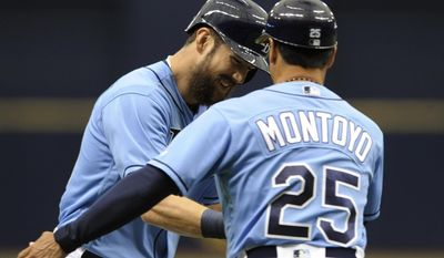 Tampa Bay Rays third base coach Charlie Montoyo (25) congratulates Steven Souza Jr., left, who hit a two-run home off Houston Astros starter Joe Musgrove during the first inning of a baseball game Sunday, April 23, 2017, in St. Petersburg, Fla. (AP Photo/Steve Nesius)