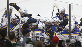 St. Louis Blues' Magnus Paajarvi (56) is swarmed with his teammates after scoring the game-winning goal during overtime in Game 5 of an NHL hockey Stanley Cup first-round playoff series against the Minnesota Wild, Saturday, April 22, 2017, in St. Paul, Minn. St. Louis won 4-3. (AP Photo/Stacy Bengs)