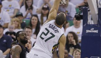 Utah Jazz center Rudy Gobert (27) goes for a rebound as Los Angeles Clippers' DeAndre Jordan, left, and Raymond Felton (2) look on during the first half in Game 4 of an NBA basketball first-round playoff series Sunday, April 23, 2017, in Salt Lake City. (AP Photo/Rick Bowmer)