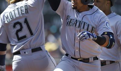 Seattle Mariners' Nelson Cruz, right, celebrates with Taylor Motter (21) after hitting a three run home run off Oakland Athletics' Raul Alcantara in the seventh inning of a baseball game, Sunday, April 23, 2017, in Oakland, Calif. (AP Photo/Ben Margot)