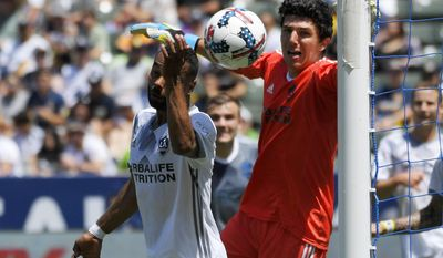 Los Angeles Galaxy goalkeeper Brian Rowe, right, and Ashley Cole, left, watch as a shot by Seattle Sounders midfielder Clint Dempsey scores during the first half of a MLS soccer match, Sunday, April 23, 2017, in Carson, Calif. (AP Photo/Mark J. Terrill)