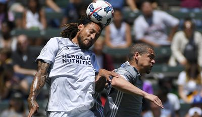 Los Angeles Galaxy midfielder Jermaine Jones, left, heads the ball as Seattle Sounders midfielder Osvaldo Alonso jumps alongside during the first half of a MLS soccer match, Sunday, April 23, 2017, in Carson, Calif. (AP Photo/Mark J. Terrill)