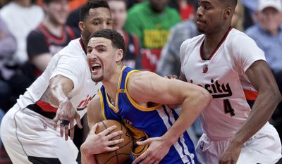 Golden State Warriors guard Klay Thompson, center, drives past Portland Trail Blazers guard Evan Turner, left, and forward Maurice Harkless, right, during the first half of Game 3 of an NBA basketball first-round playoff series Saturday, April 22, 2017, in Portland, Ore. (AP Photo/Craig Mitchelldyer)