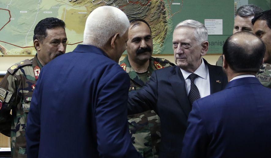 U.S. Defense Secretary James Mattis , right, consoles outgoing Afghanistan Defense Minister Abdullah Habibi  (back to camera), who resigned his post earlier in the day in the wake of a deadly attack on an Afghan base, at the start of a meeting at Resolute Support headquarters in Kabul, Afghanistan, Monday, April 24, 2017. Mattis arrived unannounced in Afghanistan to assess America's longest war as the Trump administration weighs sending more U.S. troops. (Jonathan Ernst/Pool Photo via AP)