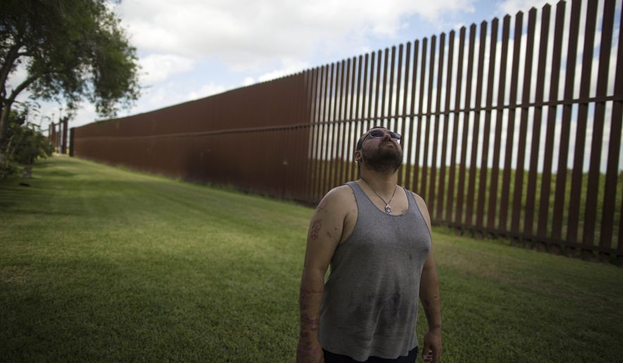 "FILE - In this March 22, 2017, file photo, Antonio Reyes of Brownsville, Texas, stands by the U.S.-Mexico border fence near his home. Reyes said he's seen people scale the border fence that bisects his backyard and jump down in seconds. Sometimes they carry bales of what appear to be drugs. A higher wall is ""still not going to stop them,"" he said. ""They'll shotput it or whatever they have to do."" (AP Photo/Rodrigo Abd, File)"