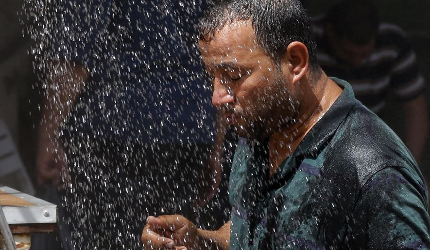 FILE - In this July 20, 2016 file photo, an Iraqi man cools off the summer heat by using an open air shower in Baghdad, Iraq. Most people on Earth have already felt extreme and record heat, drought or downpours goosed by man-made global warming, a new study finds.  (AP Photo/Karim Kadim, File)