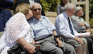 Shirley Rubin, left, kisses holocaust survivor Morric Jusovic after he spoke at a news conference in support of Boca Raton's decision to drop German insurance giant Allianz as sponsor of a professional golf tournament, Monday, April 24, 2017, in Boca Raton, Fla. Survivors say that this could renew momentum for their years-long effort to gain the right to sue the company over stolen Jewish policies during the Nazi era. (AP Photo/Lynne Sladky)